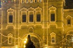 MOSKWA ROSJA, GRUDZIEŃ, - 06, 2017: Bożenarodzeniowe dekoracje na fasadowym, kolorowym wakacyjnym bokeh, zaświecają, dziewczyna w fotografia royalty free