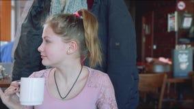 MOSKWA, ROSJA - 8 2018 hala targowa: Poważna młoda długowłosa caucasian blondynka z śnieżnobiałą skórą pije od białej filiżanki zdjęcie wideo