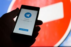 MOSKWA ROSJA, KWIECIEŃ, - 16, 2018: Telefon komórkowy z telegramem app w ręce przeciw zabrania znakowi Telegram zakazujący w Rosj obraz stock