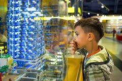 MOSKWA ROSJA, Lipiec, - 05, 2016 Chłopiec w sklepów spojrzeniach przy okno z obraz stock