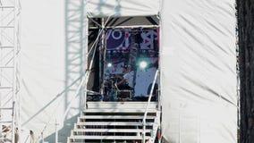 MOSKWA ROSJA, LIPIEC, - 16, 2017: Dobosz wykonuje na scenie przy festiwalem muzyki Boczny widok na scenie przez dziury bramy zbiory