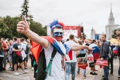 MOSKWA ROSJA, LIPIEC, - 2018: Fan piłki nożnej z twarzą malującą w kolorach rosjanin flaga z pióropuszem w fan strefie i zdjęcie stock
