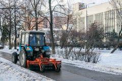 MOSKWA ROSJA, LISTOPAD, - 27, 2016: Ciągnik czyści up ulicę po noc opadu śniegu Obraz Stock