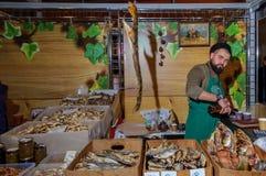 Moskwa Rosja, Luty, - 25, 2017: Brodaty sprzedawca wysuszona i uwędzona ryba w czasie przerwy przy pracą na jarmarku Zdjęcia Royalty Free