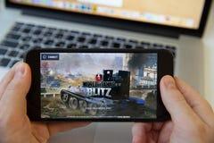 Moskwa, Rosja, Luty/- 20, 2019: trzymać iPhone na MacBook tle Świat zbiornik gra ładuje obraz royalty free