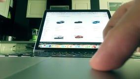 MOSKWA ROSJA, LUTY, - 25, 2018 Wybierać samochód na amazonce com sklepu online miejsce Mężczyzna używa touchpad laptop Obraz Royalty Free