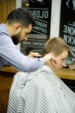 MOSKWA ROSJA, MAJ, - 24, 2018: Rosyjski fryzjer męski robi ostrzyżeniu Zdjęcia Stock