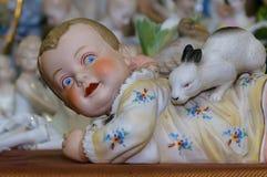 Moskwa Rosja, Marzec, - 19, 2017: Rocznik porcelany inkasowej figurki Rumiany dziecko bawić się z królikiem przy antykwarskim jar Zdjęcie Royalty Free
