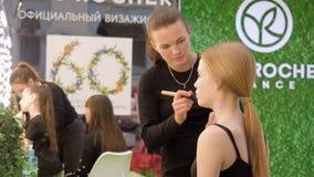 Moskwa Rosja, Marzec, - 21, 2019: visagiste stosuje kosmetyka na twarzy makeup model podczas gdy wystawa Makeup artysta zbiory wideo