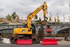 MOSKWA ROSJA, PAŹDZIERNIK, - 24, 2017: Żółty koło ekskawator Hyundai, pracuje w miastowym środowisku obok hotelowy ` Ukraina ` Obraz Royalty Free