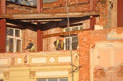 MOSKWA ROSJA, PAŹDZIERNIK, - 16, 2018: Pracownicy rozmontowywa starych domy przy budową hotelowy powikłany Sad Zaryold dom obraz stock
