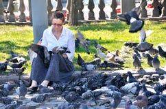 Moskwa, Rosja, Sierpień, 21, 2016 Kobieta żywieniowi gołębie w Ilyinsky obciosują w lecie Obraz Royalty Free