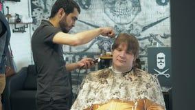 MOSKWA, ROSJA STYCZEŃ 12, 2018: Fryzjer ciie długie włosy z tyłu głowy klient w salonie Mężczyzna obsiadanie wewnątrz zdjęcie wideo