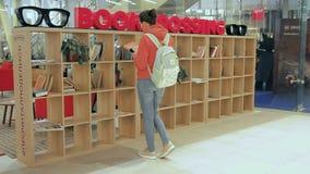 Moskwa Rosja, Wrzesień, - 16, 2018: Dziewczyna wybiera książkę na półce BookCrossing Drewniany odkładać z książkami zbiory