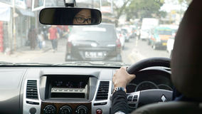 A moslem asian women driving a car in a traffic jam Stock Image