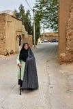 Moslemische ältere Frau, gekleidet im schwarzen Chador auf der Straße der alten Stadt in Yazd iran Stockfotografie
