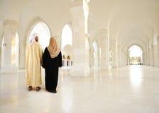 Moslemische arabische Paare innerhalb des modernen Gebäudes Stockfotografie