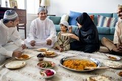 Moslemische Familie, die auf dem Boden zu Abend isst lizenzfreies stockbild