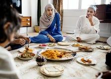 Moslemische Familie, die auf dem Boden zu Abend isst stockfotografie