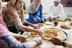 Moslemische Familie, die auf dem Boden zu Abend isst stockbilder