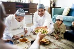 Moslemische Familie, die auf dem Boden zu Abend isst stockfoto