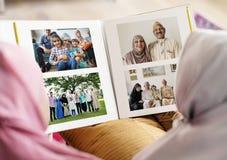 Moslemische Familie, die in einem Fotoalbum schaut stockfotos