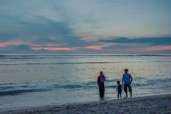 Moslemische Familie, die entlang den Strand im Sonnenuntergang geht Lizenzfreie Stockbilder
