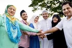 Moslemische Familie, die Hände im Park stapelt lizenzfreie stockfotografie