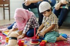 Moslemische Familie, die sich zu Hause entspannt und spielt stockfotografie