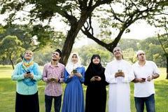 Moslemische Familie, die Smartphone im Park hält lizenzfreie stockfotos