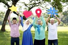 Moslemische Familie, die verschiedene Social Media-Ikonen hält stockfotografie