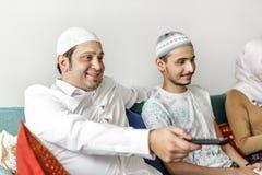 Moslemische Familie, die zu Hause fernsieht lizenzfreie stockfotos