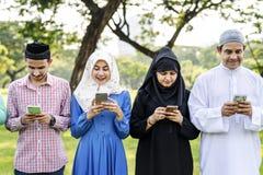 Moslemische Familie genießen, Smartphones im Park zu verwenden stockfoto