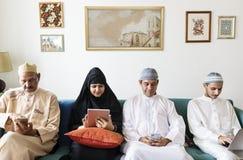 Moslemische Familie unter Verwendung der digitalen Geräte zu Hause lizenzfreies stockbild