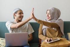 Moslemische Familie unter Verwendung der digitalen Geräte zu Hause stockbild