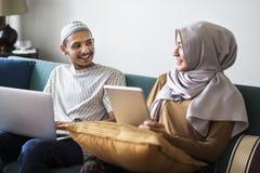Moslemische Familie unter Verwendung der digitalen Geräte zu Hause lizenzfreie stockbilder