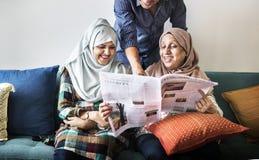 Moslemische Familie, welche die Nachrichten liest stockbilder