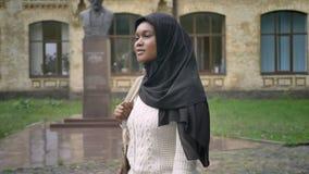 Moslemische Frau des schönen Afroamerikaners im hijab gehend in Park nahe Universität, reizend Studentin, Bürgersteig stock footage