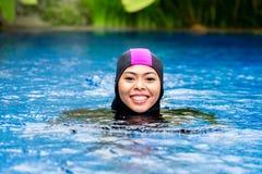 Moslemische Frau, die Burkini-Badebekleidung im Pool trägt Stockfotografie
