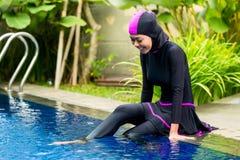 Moslemische Frau, die Burkini-Badebekleidung am Pool trägt Stockfotografie