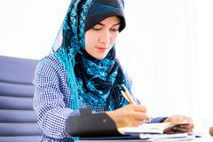 Moslemische Frau, die digitale Tablette auf Bürotisch verwendet lizenzfreie stockfotografie