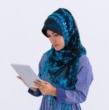 Moslemische Frau, die digitale Tablette auf Weiß verwendet lizenzfreie stockfotos