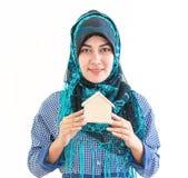 Moslemische Frau, die ein Hausmodell für Unterkunftkonzept hält lizenzfreie stockbilder
