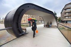Moslemische Frau mit buntem Regenschirm auf Sestina-lente, Fußgängerbrücke über Miljacka-Fluss Lizenzfreie Stockfotos