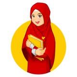 Moslemische Frau mit dem Umarmen eines Buches, das roten Schleier trägt