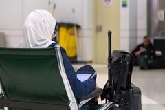 Moslemische Frau, welche die traditionelle Kleidung sitzt und betrachtet Tablette trägt Lizenzfreie Stockbilder