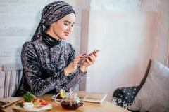 Moslemische Frauen, die smartphonephone halten Denken an gute Gedächtnisse stockfotos