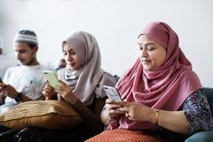 Moslemische Freunde, die Social Media an den Telefonen verwenden lizenzfreie stockfotografie