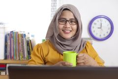 Moslemische Geschäftsfrau Taking Coffee Break im Büro lizenzfreies stockfoto