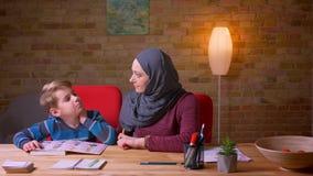 Moslemische Mutter im hijab Buchstaben mit ihrem kleinen Sohn am Tisch zu Hause lernend stock footage
